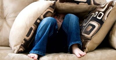 child hiding under cushions